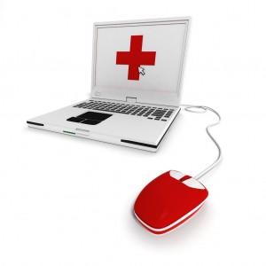 laptop z czerwonym krzyżem imyszką